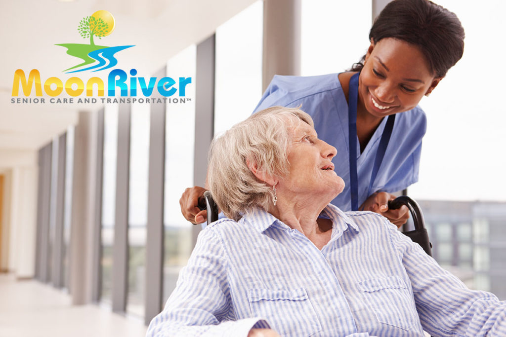 Nurse Pushing Senior Patient In Wheelchair - Moon River Senior Care